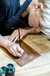 Burberry's artist flown in from London hand painting initials