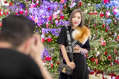 Faye Tsui poses underneath the Christmas Tree as she gets her photograph taken
